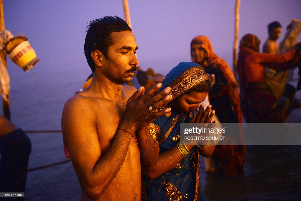 Indian Hindu devotees pray as they bathe in the Sangham or confluence of the Yamuna and Ganges rivers at dawnduring the Kumbh Mela in Allahabad on January 14, 2013. Hundreds of thousands of Hindu pilgrims led by naked, ash-covered holy men streamed into the sacred river Ganges at the start of the world's biggest religious festival. The Kumbh Mela in the Indian town of Allahabad will see up to 100 million worshippers gather over the next 55 days to take a ritual bath in the holy waters, believed to cleanse sins and bestow blessings.