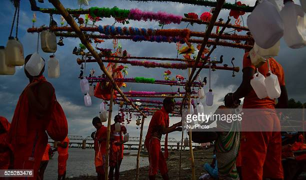 Indian hindu devotees prepare for their Kanwar yatra as they take holy water of River Ganga in plastic containors on the sacred month of Shravan at...