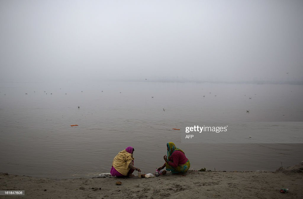 Indian Hindu devotees prepare offerings at the Sangam or confluence of the Yamuna, Ganges and mythical Saraswati rivers at the Kumbh Mela in Allahabad on February 17, 2013. The Kumbh Mela in the town of Allahabad will see up to 100 million worshippers gather over 55 days to take a ritual bath in the holy waters, believed to cleanse sins and bestow blessings. AFP PHOTO/ Andrew Caballero-Reynolds