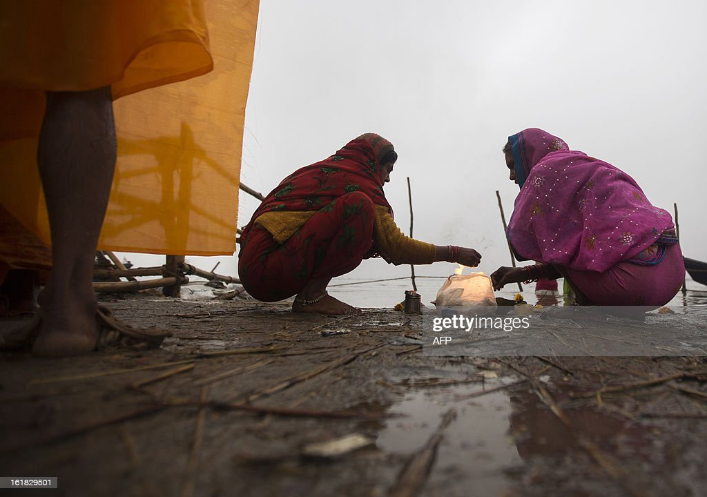 Indian Hindu devotees prepare offerings for prayer at the Sangam or confluence of the Yamuna, Ganges and mythical Saraswati rivers during the Kumbh Mela in Allahabad on February 17, 2013. The Kumbh Mela in the town of Allahabad will see up to 100 million worshippers gather over 55 days to take a ritual bath in the holy waters, believed to cleanse sins and bestow blessings. AFP PHOTO/ Andrew Caballero-Reynolds