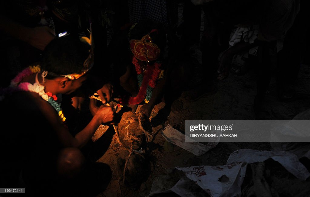 Indian Hindu devotees prepare to parade with human remains during the Shiva Gajan festival in Kurmun, a remote village some 160 kilometres (99 miles) west of Kolkata on April 13, 2013. Shiva-Gajan is a traditional festival performed on the last day of Bengali calendar year when members of the community exhume body parts from graveyards and carry them in a procession to appease Hindu Lord Shiva. AFP PHOTO/Dibyangshu SARKAR