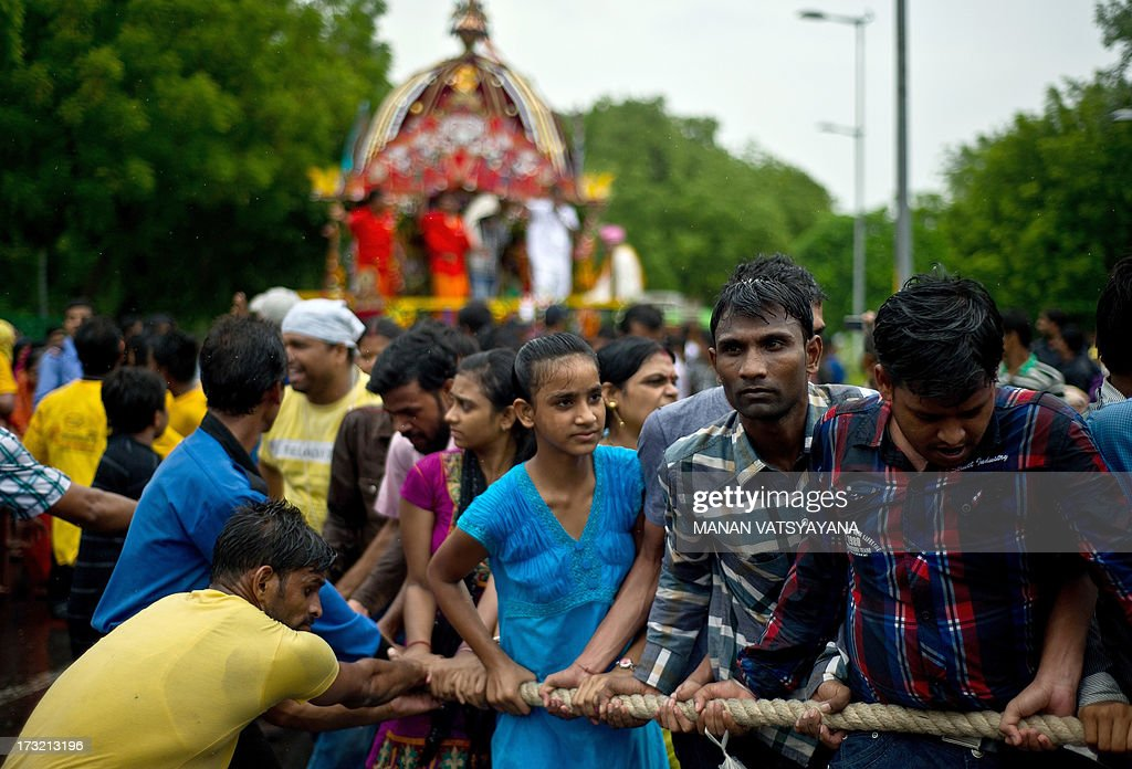 Indian Hindu devotees pull Lord Jagannath's chariot during Rath Yatra celebrations in New Delhi on July 10, 2013. This year marks the 136th annual Rath Yatra, where wooden images or idols of Lord Jagannath, his brother Balabhadra and sister Subhadra are mounted on ceremonial chariots and taken out in a procession with the participation of thousands of devotees.