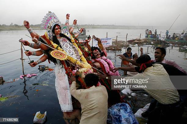 Indian Hindu devotees push an idol of the Goddess Durga into the River Yamuna for immersion in New Delhi 21 October 2007 on the final day of the...