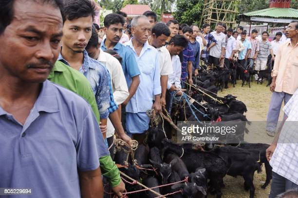Indian Hindu devotees queue with their goats before scarifying them as a part of a religious ritual during the traditional Kharchi puja festival at...