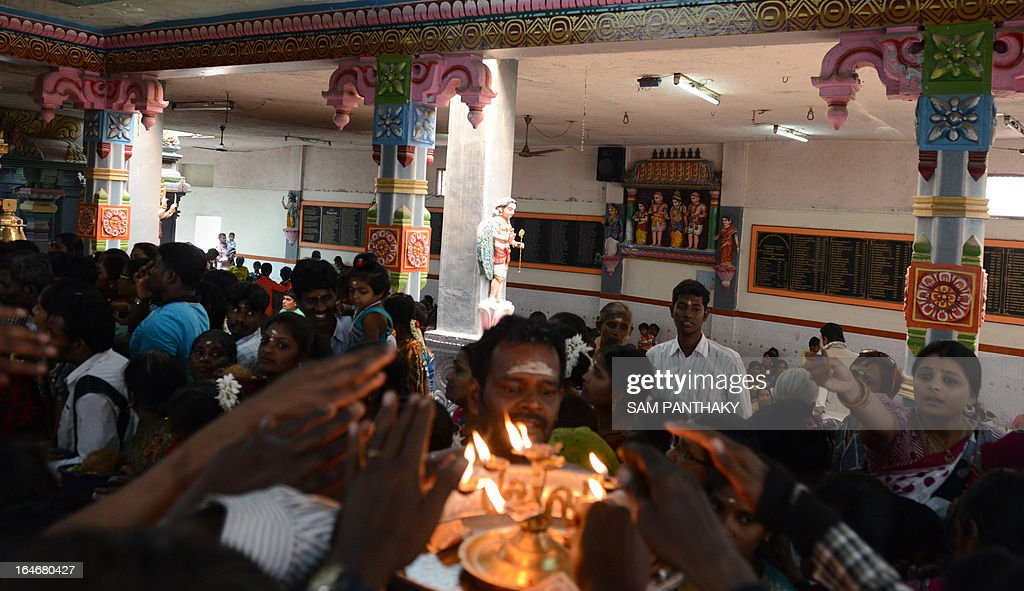 Indian Hindu devotees reach out to a Hindu priest holding lit oil lamps at Sri Balamurugan Devasthanam Trust, also known as Kartikswami Mandir, to mark the celebration of Panguni Uthiram Festival in Hatkeshwar area of Ahmedabad on March 26, 2013. Panguni Uthiram is a very important day for Tamil Hindus and it is believed that most divine marriages took place on this day. AFP PHOTO / Sam PANTHAKY