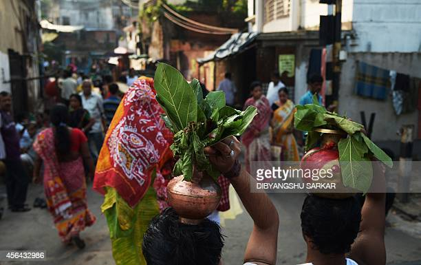 Indian Hindu devotees return after performing a ritual with banana trees wrapped saris to symbolise the wife of the Hindu god Ganesha on the river...