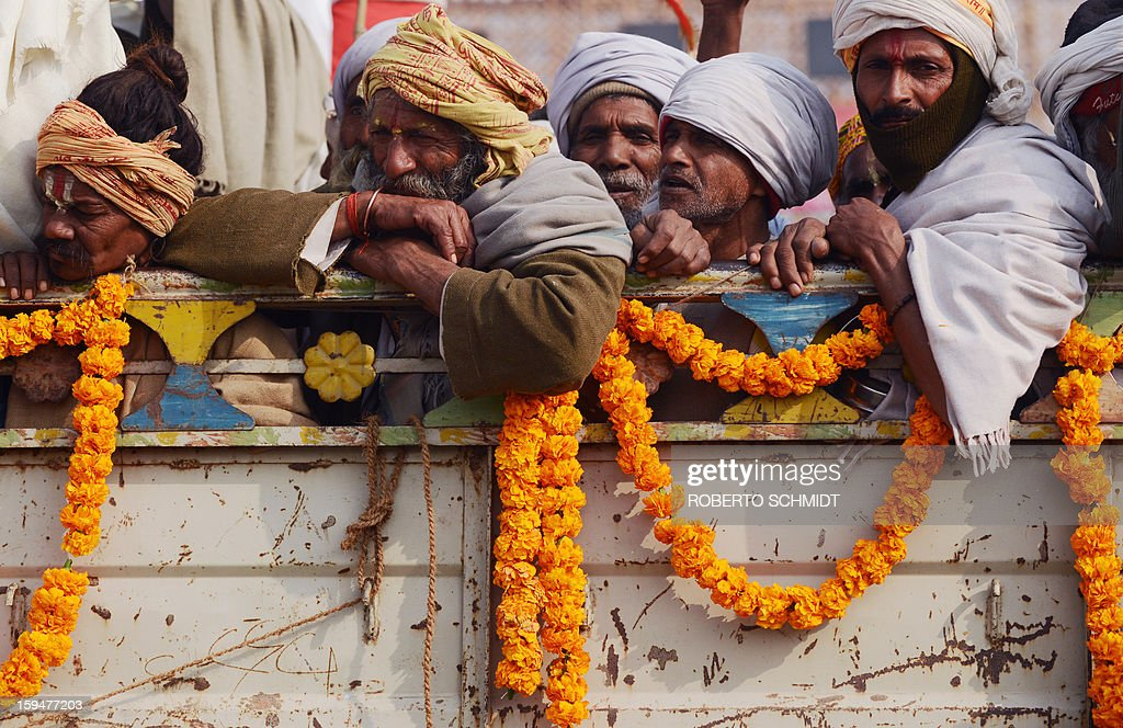 Indian Hindu devotees ride in the back of a truck during the Kumbh Mela in Allahabad on January 14, 2013. Hundreds of thousands of Hindu pilgrims led by naked, ash-covered holy men streamed into the sacred river Ganges at the start of the world's biggest religious festival. The Kumbh Mela in the Indian town of Allahabad will see up to 100 million worshippers gather over the next 55 days to take a ritual bath in the holy waters, believed to cleanse sins and bestow blessings.