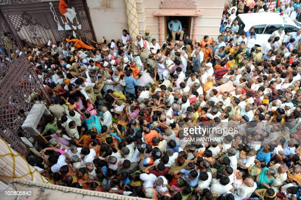 Indian Hindu devotees rush the main gate as police and volunteers attempt to control the surging crowd at the Lord Jagannath Mandir entrance in...