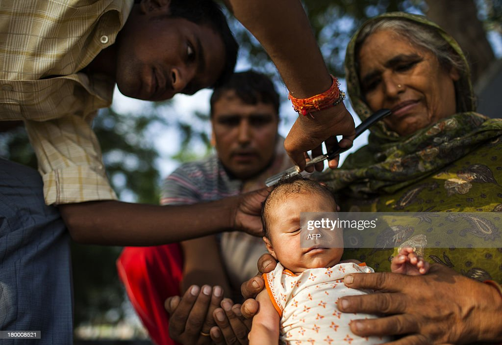 Indian Hindu devotees shave the head of an infant as part of a religious tradition at a temple in New Delhi on September 8, 2013. India is the birthplace of four of the world's major religions -- Hinduism, Buddhism, Jainism and Sikhism. AFP PHOTO/ Andrew Caballero-Reynolds