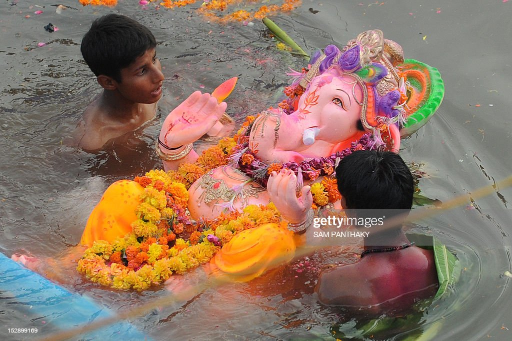 Indian Hindu devotees swim with an idol of Lord Ganesha in an artificial pond, dug for the ongoing Ganesh Chathurthi festival to help control pollution and waste, along the banks of the Sabarmati river in Ahmedabad on September 28, 2012. Hindu devotees bring home idols of Lord Ganesha during the 'Ganesh Chaturthi' in order to invoke his blessings for wisdom and prosperity, during the eleven day long festival which culminates with the immersion of the idols AFP PHOTO / Sam PANTHAKY