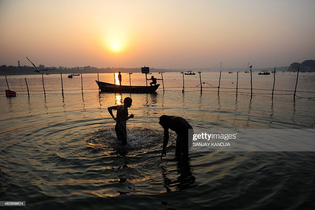 Indian Hindu devotees take a dip at Sangam the confluence of the Rivers Ganges Yamuna and mythical Saraswati during the annual Magh Mela in Allahabad...