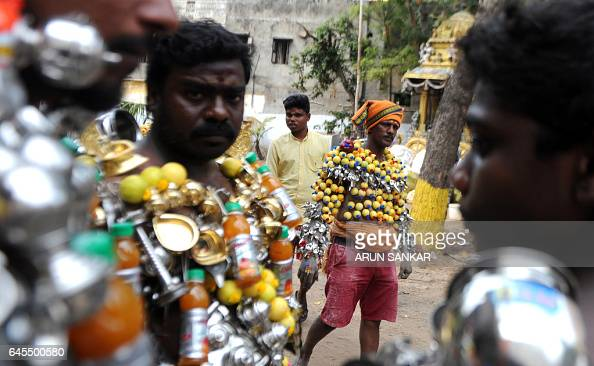 Indian Hindu devotees their bodies pierced with lemon and paladai bowl with a spout mainly used to feed milk to infants wait to participate in a...