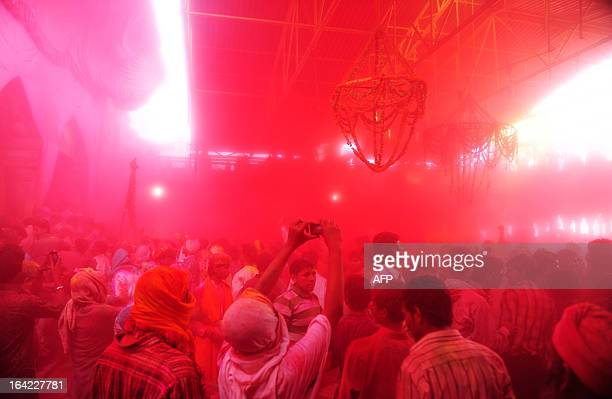 Indian Hindu devotees throw coloured powder at the Radha Rani temple during the Lathmar Holi festival in Barsana on March 21 2013 Lathmar Holi is a...