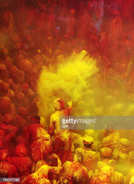 Indian Hindu devotees throw coloured powder at the Radha Rani temple during the Lathmar Holi festival in Barsana on March 21 2013 Lathmar Holi is a...