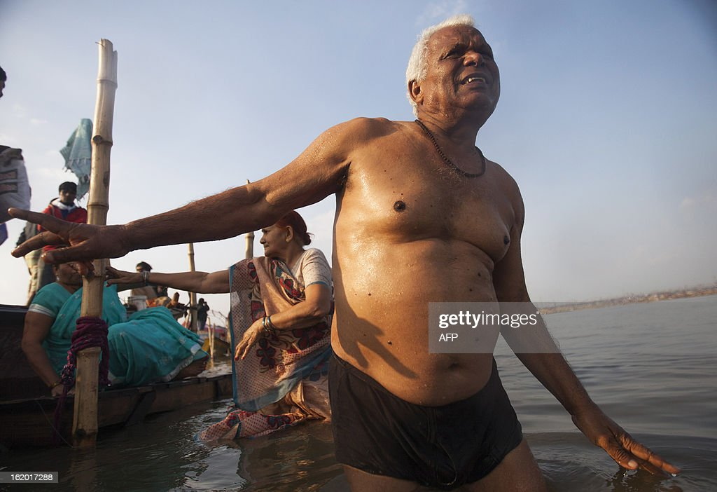 Indian Hindu devotees wade into the Sangam or confluence of the Yamuna, Ganges and mythical Saraswati rivers to bathe at the Kumbh Mela in Allahabad on February 18, 2013. The Kumbh Mela in the town of Allahabad will see up to 100 million worshippers gather over 55 days to take a ritual bath in the holy waters, believed to cleanse sins and bestow blessings. AFP PHOTO/ Andrew Caballero-Reynolds