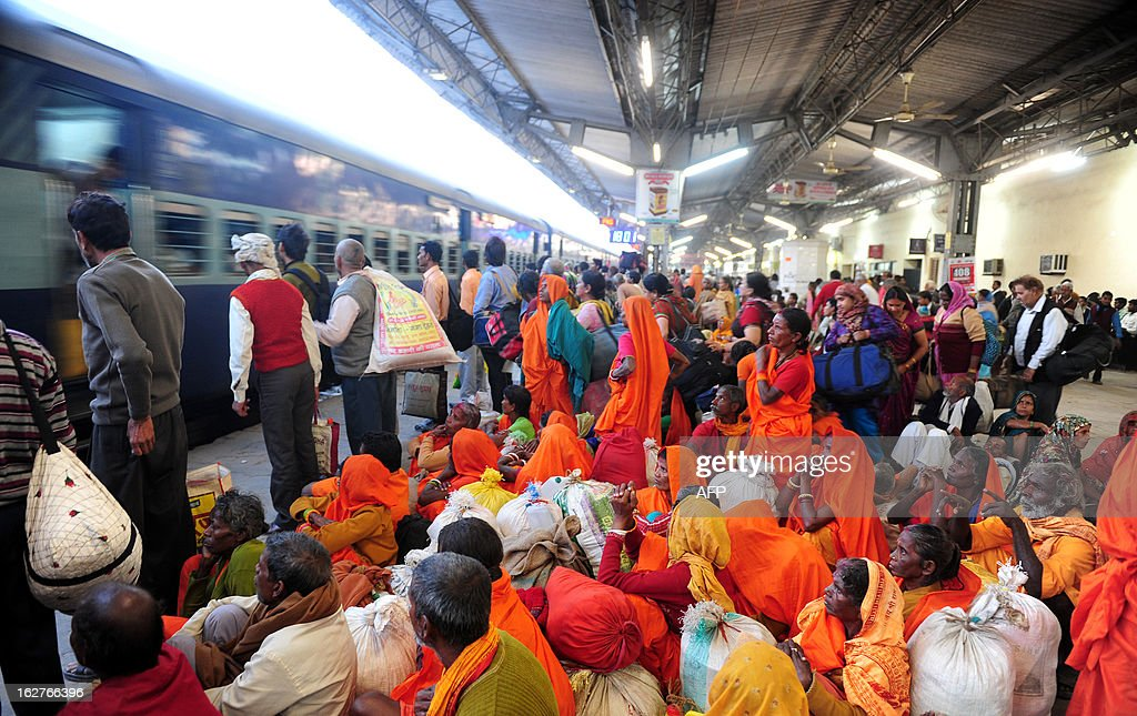 Indian Hindu devotees wait for their train at the Daraganj railway station in Allahabad on February 26, 2013. The railway, the country's largest employer with some 1.4 million people on its payroll, runs 11,000 passenger and freight trains and carries 19 million people daily. AFP PHOTO/ Sanjay KANOJIA