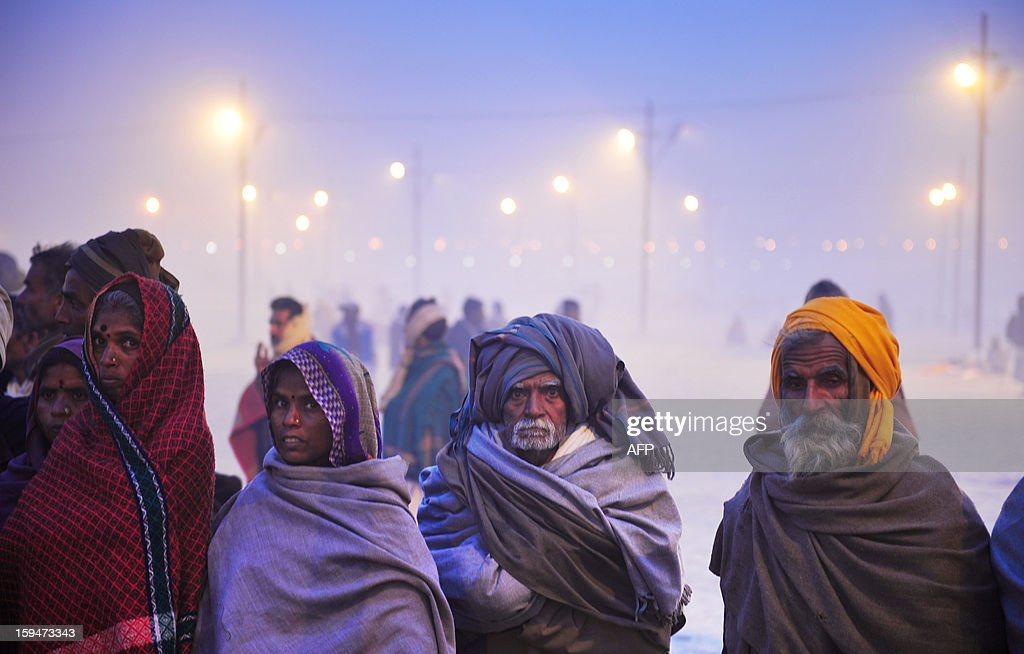 Indian Hindu devotees wait to see a procession by Sadhus as the holy men make their way to bathe in the Sangham or the confluence of the the Yamuna and Ganges rivers during the Kumbh Mela in Allahabad on January 14, 2013. Hundreds of thousands of Hindu pilgrims led by naked, ash-covered holy men streamed into the sacred river Ganges at the start of the world's biggest religious festival. The Kumbh Mela in the Indian town of Allahabad will see up to 100 million worshippers gather over the next 55 days to take a ritual bath in the holy waters, believed to cleanse sins and bestow blessings. AFP PHOTO/ Sanjay Kanojia