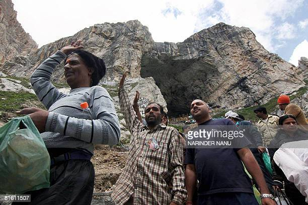 Indian Hindu devotees walk out of the holy Amarnath Cave after paying their respects before the Shiva Lingam an ice stalagmite shaped as a fallus and...