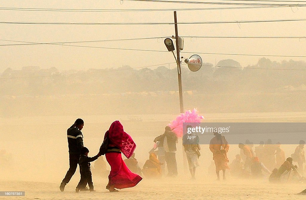 Indian Hindu devotees walk through a dust storm at the Sangam after taking a holy dip at the confluence of the rivers Ganges, Yamuna and mythical Saraswati during the Maha Kumbh festival in Allahabad on February 5, 2013. The Kumbh Mela in the town of Allahabad will see up to 100 million worshippers gather over 55 days to take a ritual bath in the holy waters, believed to cleanse sins and bestow blessings. AFP PHOTO/Sanjay KANOJIA
