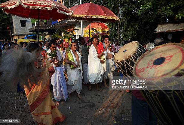 Indian Hindu devotees walk to where they will perform a ritual with banana trees wrapped saris to symbolise the wife of the Hindu god Ganesha on the...