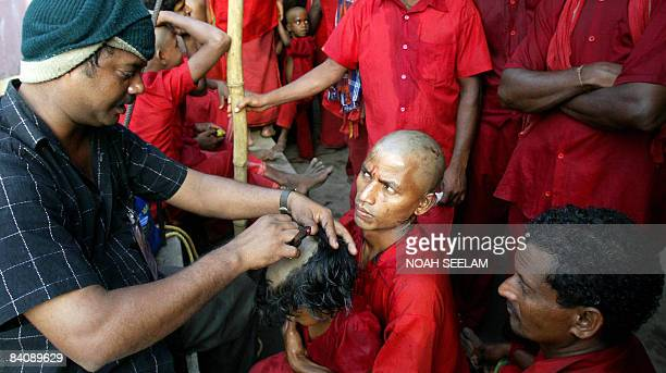 Indian Hindu devotees wearing traditional red robes have their heads shaved by a barber as they perform the final stage of Bhavani Deeksha at a...