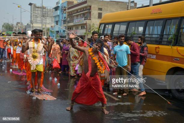 Indian Hindu devotees with steel rod piercings through their cheeks dance during a procession to honour the Hindu goddess Maha Mariamman to mark...