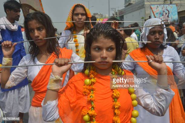 Indian Hindu devotees with steel rod piercings through their cheeks walk while taking part in a procession to honour the Hindu goddess Maha Mariamman...