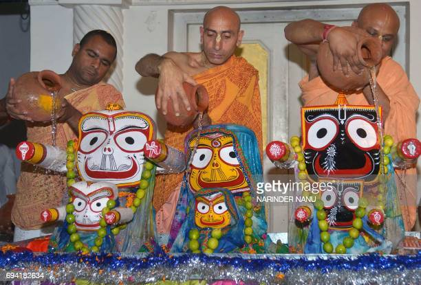 Indian Hindu devotees with the International Society of Krishna Consciousness pour water onto idols of the Hindu deity Jagannath his brother...