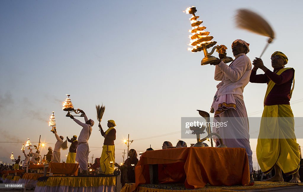 Indian Hindu holy men perforn evening prayers as the sun sets on February 17, 2013 during the Kumbh Mela festival in Allahabad. The Kumbh Mela in the town of Allahabad will see up to 100 million worshippers gather over 55 days to take a ritual bath in the holy waters, believed to cleanse sins and bestow blessings. The Kumbh Mela, which ends in March, takes place every 12 years in Allahabad. AFP PHOTO / Andrew Caballero-Reynolds