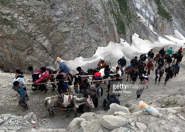 Indian Hindu pilgrims cross ice and snow during their religious journey to the Amarnath cave via Baltal route some 125 kilometers northeast of...