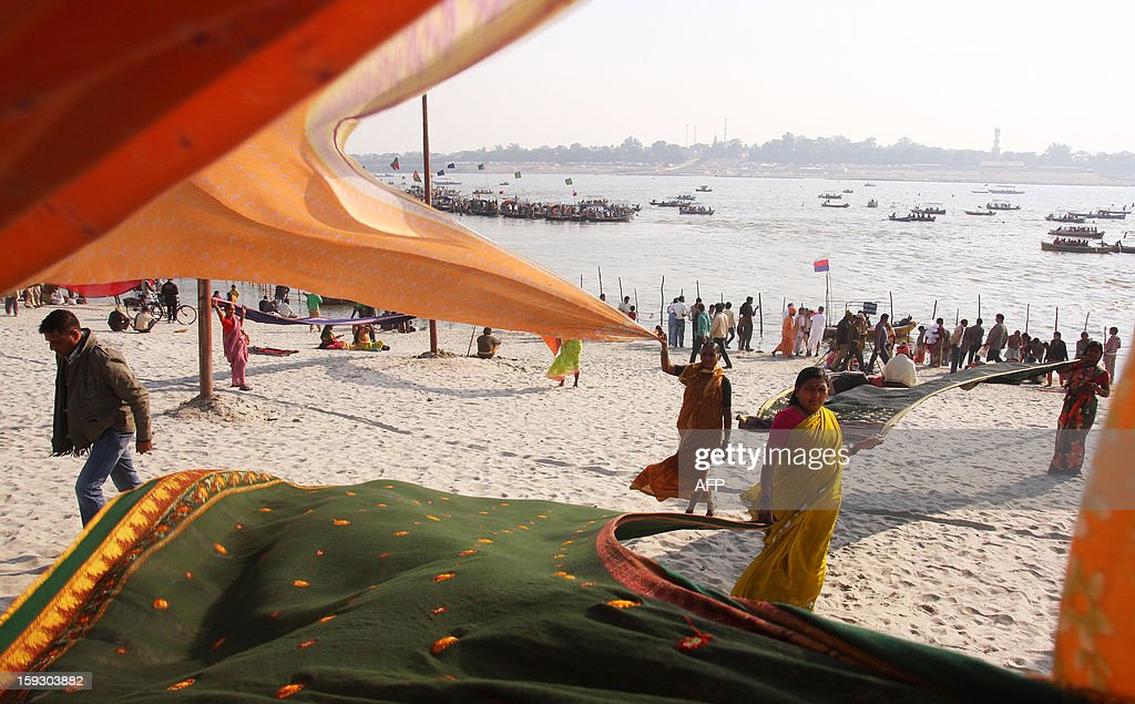 Indian Hindu pilgrims dry their saris after a holy dip on the banks of Sangam, the confluence of rivers Ganges, Yamuna and mythical Saraswati in Allahabad on January 11, 2013. The Kumbh Mela, which is scheduled to take place in the northern Indian city in January and February 2013, is the world's largest gathering of people for a religious purpose and millions of people gather for this auspicious occasion. AFP PHOTO/ Sanjay KANOJIA