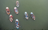 Indian Hindu pilgrims travel on boats to take a holy dip at Sangam the confluence of the Rivers Ganges Yamuna and the mythical Saraswati during the...