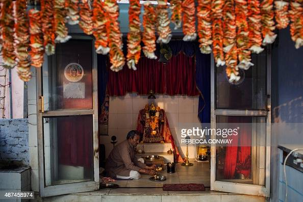Indian Hindu priest Pandit Madan Mohan Mishra offers a daily morning prayer during a puja ceremony at the Kalimata Mandir temple at a 'dhobi ghat'...
