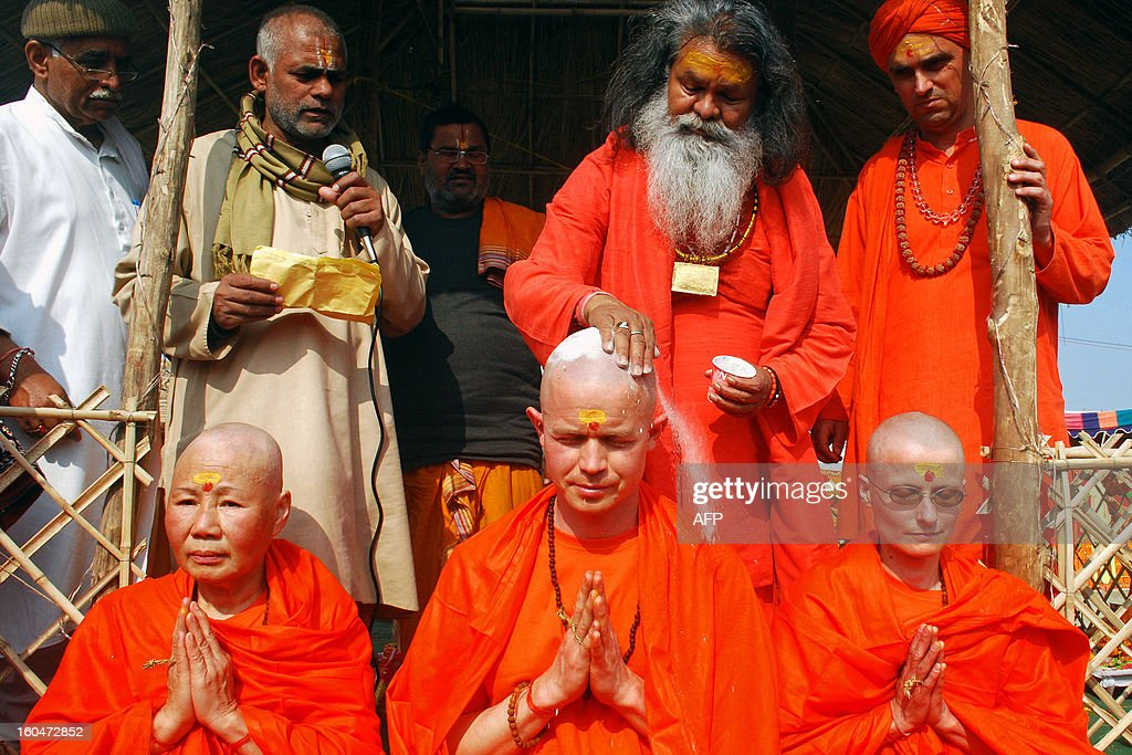 Indian Hindu priest Swami Maheshwaranand Puri (2nd L, top), applies ash as he performs a religious ritual for foreign Hindu devotees Catherine Yutming of China, Juraj from Slovakia, and Patricia from the Czech Republic during the Maha Kumbh festival in Allahabad on February 1, 2013. The Kumbh Mela in the town of Allahabad will see up to 100 million worshippers gather over 55 days to take a ritual bath in the holy waters, believed to cleanse sins and bestow blessings. AFP PHOTO/Sanjay KANOJIA