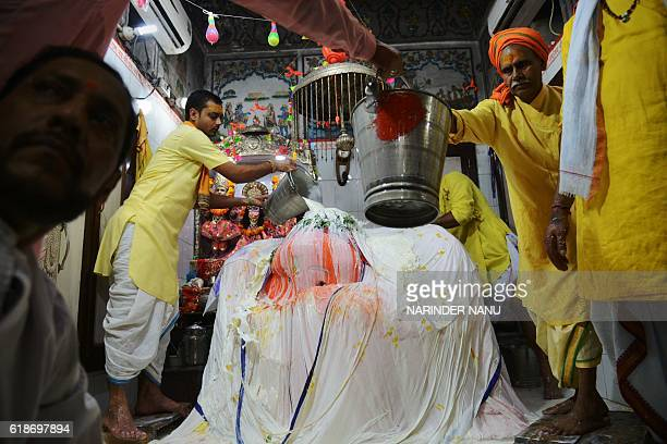 Indian Hindu priests bathe a statue of the Hindu god Hanuman with seven tonnes or approximately 7000 litres of milk at the Bara Hanuman Temple in...
