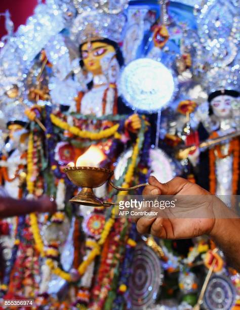 Indian Hindu priests perform rituals to worship sixyear old Hindu girl Anushka Chetterjee dressed as the Hindu goddess Durga to a 'pandal' the...