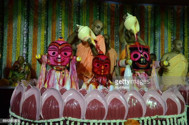 Indian Hindu priests pour milk honey curd and water on idols of Lord Jagannath Balabhadra and Subhadra on the occasion of holy Snan Yatra or bathing...
