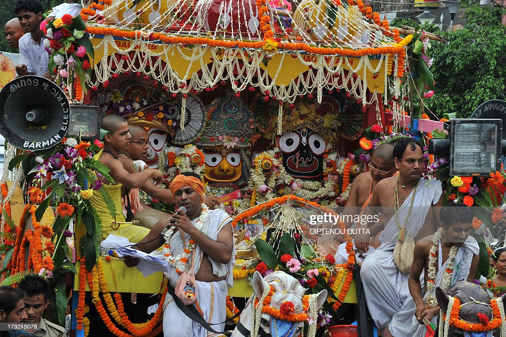 Indian Hindu priests sit on the chariot as devotees pull Lord Jagannath's chariot during Rath Yatra celebrations in Siliguri on July 10, 2013. This year marks the 136th annual Rath Yatra, where wooden images or idols of Lord Jagannath, his brother Balabhadra and sister Subhadra are mounted on ceremonial chariots and taken out in a procession with the participation of thousands of devotees. AFP PHOTO/Diptendu DUTTA