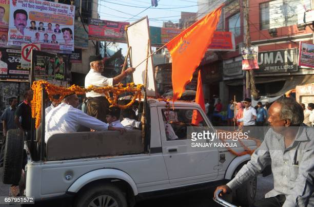 Indian Hindu Rashtriya Swayamsevak Sangh volunteers wave a flag in a vehicle as they take part in a march during an event in Allahabad on March 26...