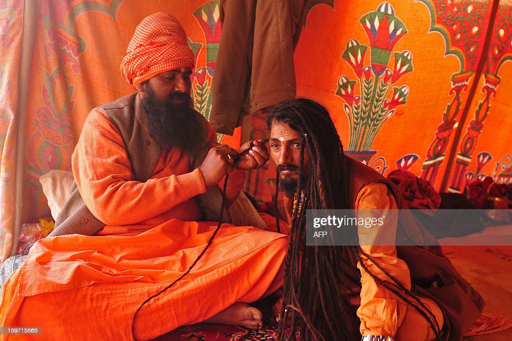 A Indian Hindu Saddhu (holy man) braids the dreadlocks of another devotee near Sangam, the confluence of the Rivers Ganges, Yamuna and mythical Saraswati, during the Maha Kumbh Mela in Allahabad on January 19, 2013. The Kumbh Mela in the Indian town of Allahabad will see up to 100 million worshippers gather over the next 55 days to take a ritual bath in the holy waters, believed to cleanse sins and bestow blessings. AFP PHOTO/ Sanjay KANOJIA