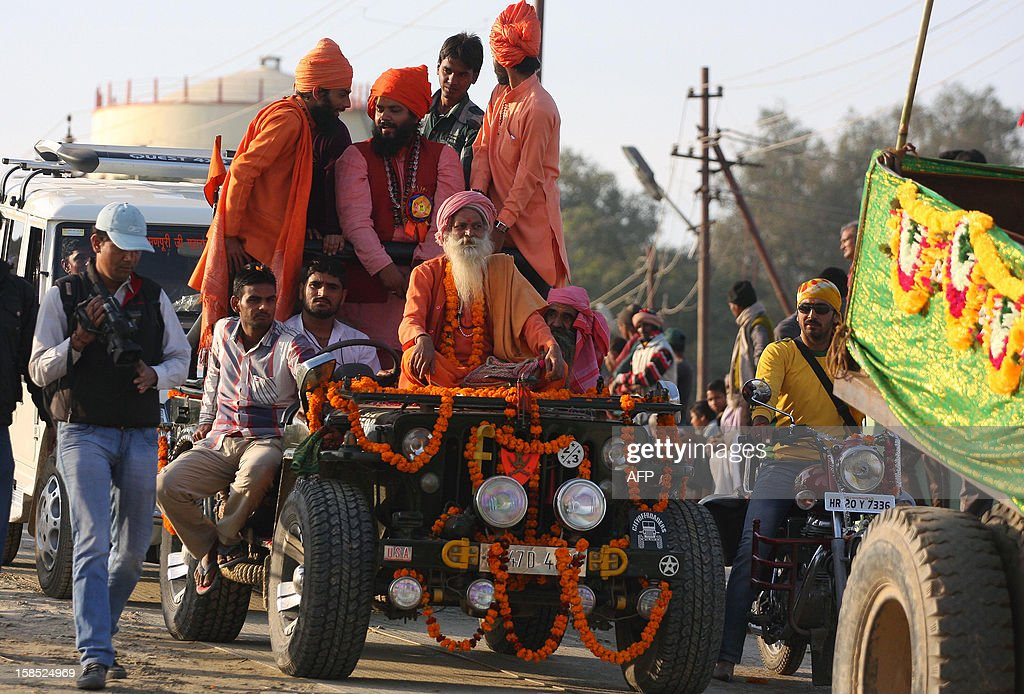 Indian Hindu Sadhus (holy men) from the Juna Akhara ride on a jeep as they take part in a religious procession towards Sangam in Allahabad on December 18, 2012, the first 'Royal Entry' to the Kumbh Mela. The Kumbh Mela, which is scheduled to take place in the northern Indian city in January and February 2013, is theworld's largest gathering of people for a religious purpose and millions of people gather for this auspicious occasion. AFP PHOTO/Sanjay KANOJIA