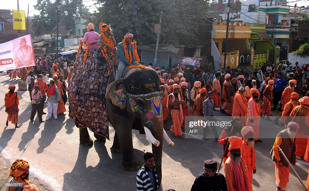 Indian Hindu Sadhus (holy men) from the Juna Akhara walk with an elephant as they take part in a religious procession towards Sangam in Allahabad on December 18, 2012, the first 'Royal Entry' to the Kumbh Mela. The Kumbh Mela, which is scheduled to take place in the northern Indian city in January and February 2013, is theworld's largest gathering of people for a religious purpose and millions of people gather for this auspicious occasion. AFP PHOTO/Sanjay KANOJIA