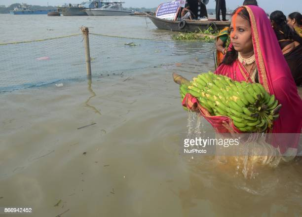 Indian Hindu woman devotee offering prayers to the Sun God on the banks of river Ganges in Kolkata India on Thursday 26th October 2017 The Chhath...
