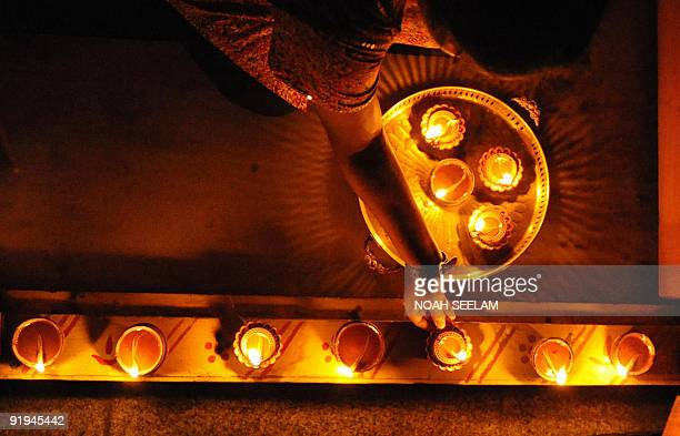 Indian Hindu woman Trisha decorates the entrance of her home with diyas on the eve of Diwali the festival of lights in Hyderabad on October 16 2009...
