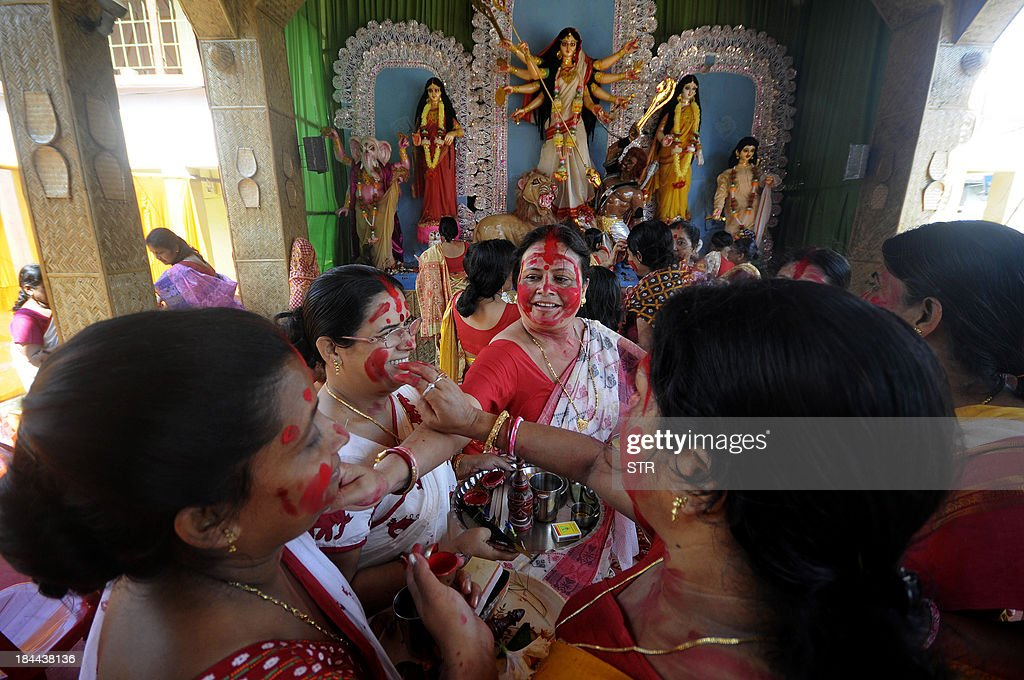 Indian Hindu women devotees apply vermillion powder to each other as a ritual during Dashami, the last day of Durga Puja festival at Agartala, the capital of northeastern state of Tripura on October 14, 2013. The festival which honours the Hindu Goddess Durga is celebrated by Hindu's across the world.