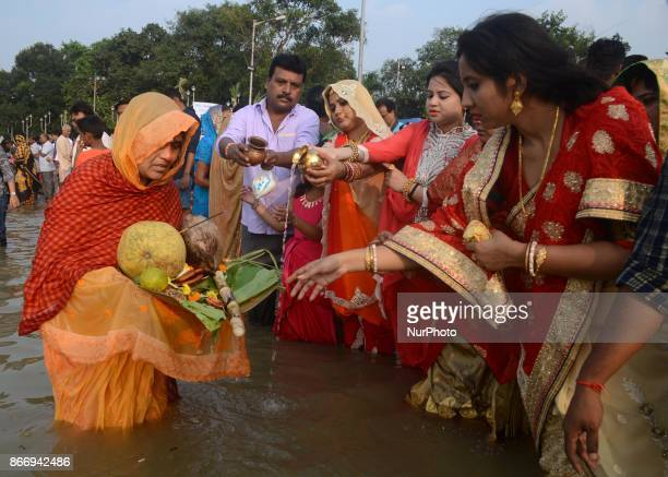Indian Hindu women devotees offering prayers to the Sun God on the banks of river Ganges in Kolkata India on Thursday 26th October 2017 The Chhath...