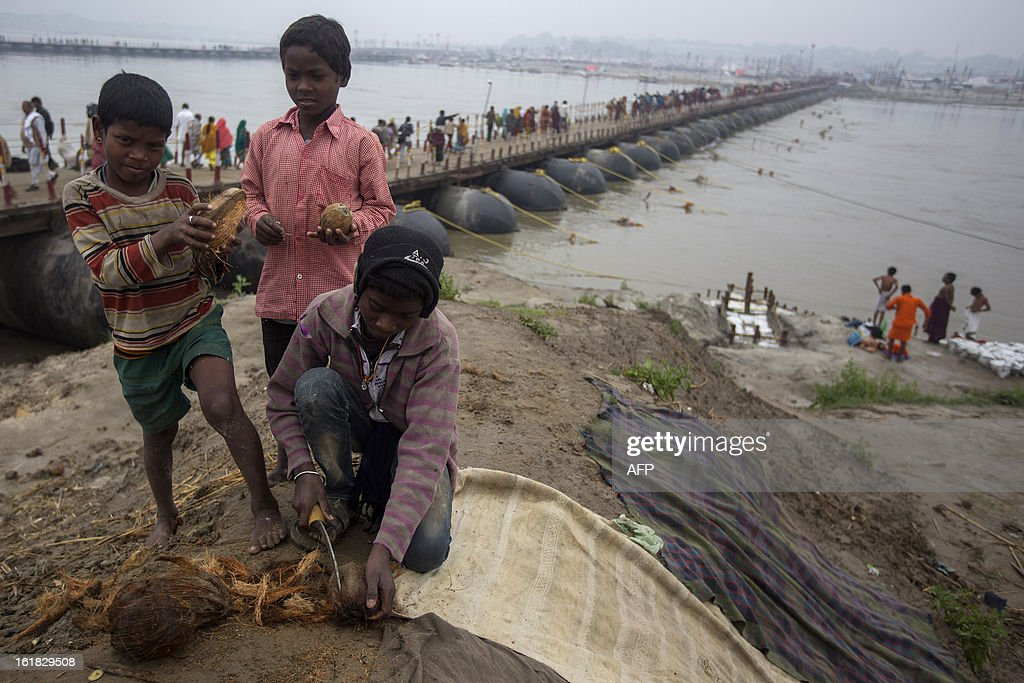 Indian Hindu youth cut coconuts to sell to devotees as offerings near the Sangam or confluence of the Yamuna, Ganges and mythical Saraswati rivers during the Kumbh Mela in Allahabad on February 17, 2013. The Kumbh Mela in the town of Allahabad will see up to 100 million worshippers gather over 55 days to take a ritual bath in the holy waters, believed to cleanse sins and bestow blessings. AFP PHOTO/ Andrew Caballero-Reynolds
