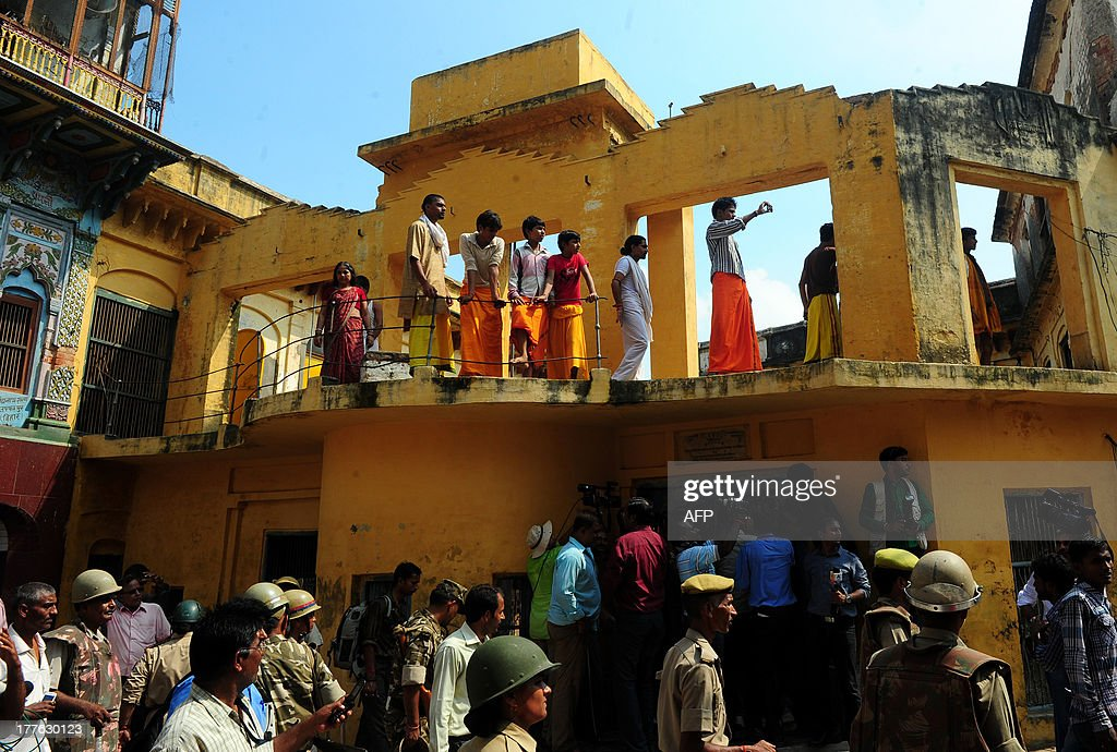 Indian Hindu youth of the Veda Vidyalaya watch from a window as Indian soldiers patrol in Ayodhya on August 25, 2013. Indian police arrested leaders of a Hindu forum to try and prevent a march to a pilgrimage town where the 1992 razing of a mosque sparked deadly sectarian riots. Organisers from the Vishwa Hindu Parishad (VHP, World Hindu Council) and the Press Trust of India (PTI) said some 125 people were detained in the northern state of Uttar Pdaesh.