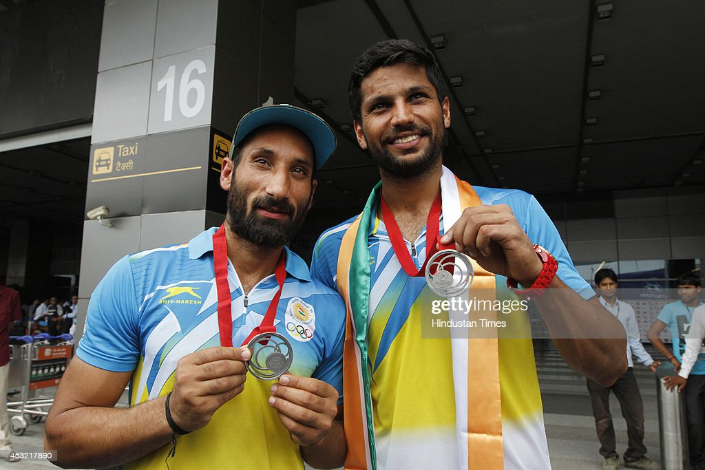 Indian hockey captain Sardar Singh with his teammate Rupinder Pal Singh show their silver medals on arrival at the IGI Airport after participating in CWG 2014 held at Glasgow on August 5, 2014 in New Delhi, India.
