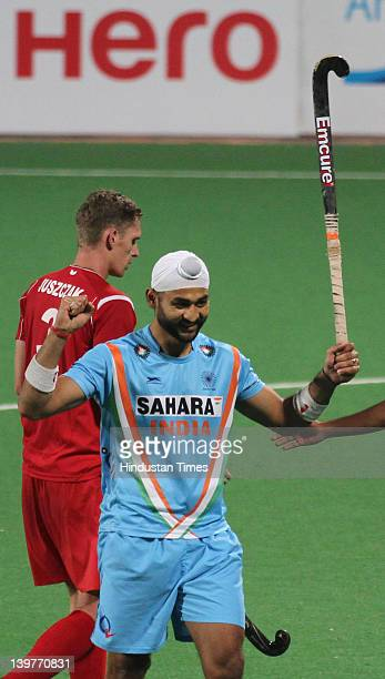 Indian hockey player Sandeep Singh celebrates with team members after victory during the FIH London Olympics men's hockey qualifying match between...